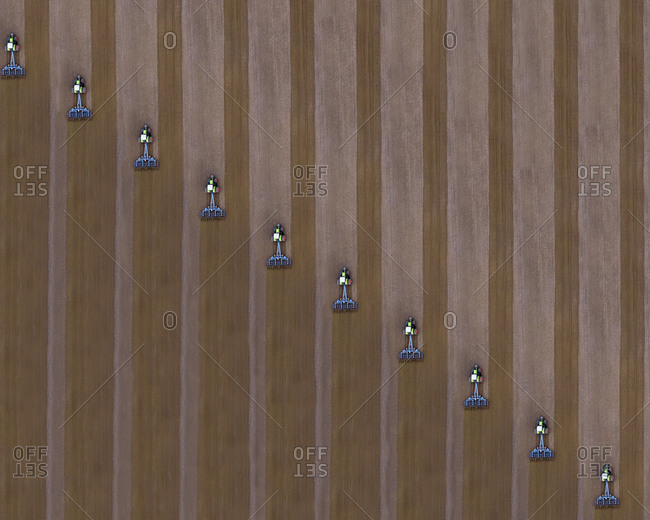 Russia- Aerial view of tractors plowing brown field