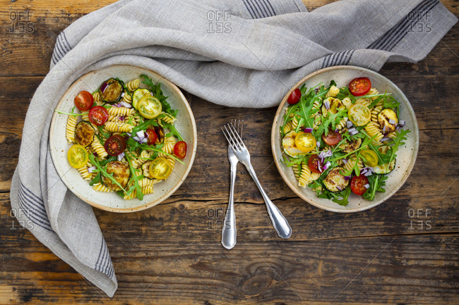 Two bowls of pasta salad with grilled zucchini- tomatoes- arugula- Spanish onion and balsamic vinegar
