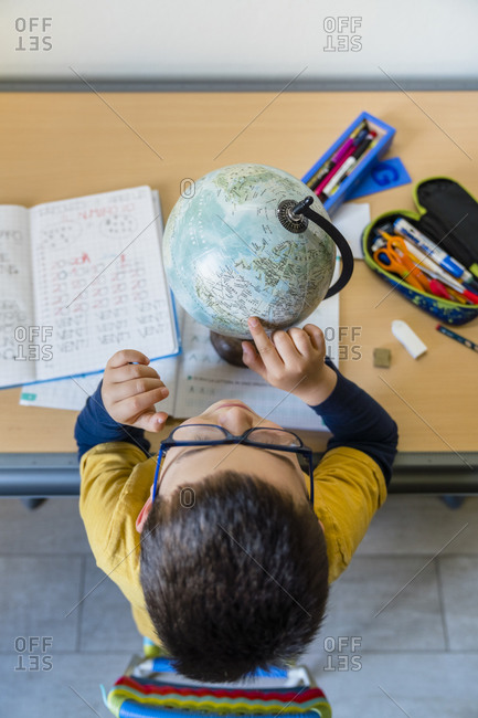 Directly above view of boy examining globe at desk during homeschooling