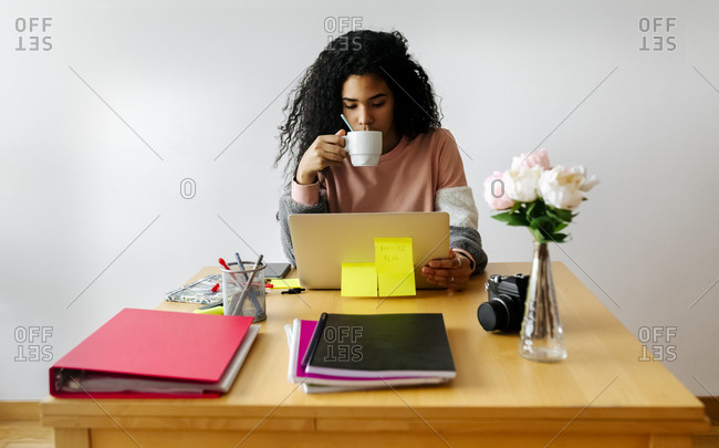 Young woman working from home using laptop and drinking coffee