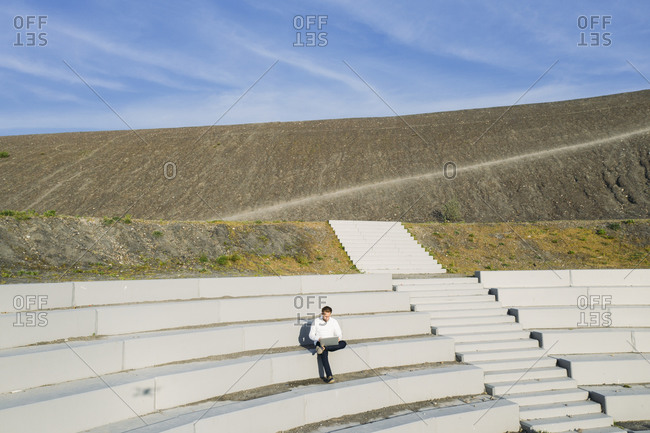 Businessman sitting with laptop at BergArena amphitheater steps against sky on sunny day