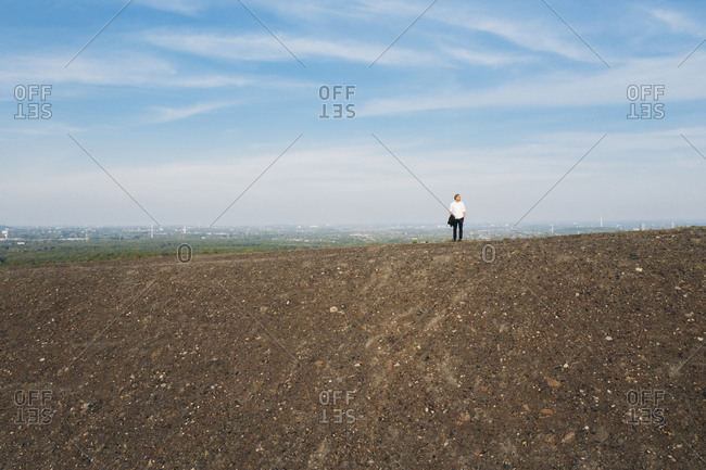 Full length of mature businessman standing on hill against sky