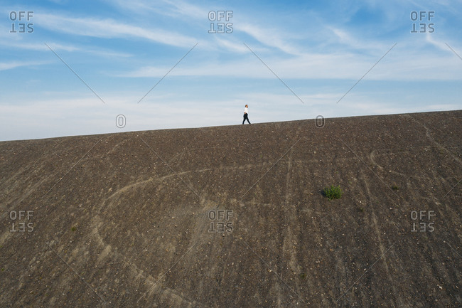 Low angle view of male professional walking on hill during sunny day