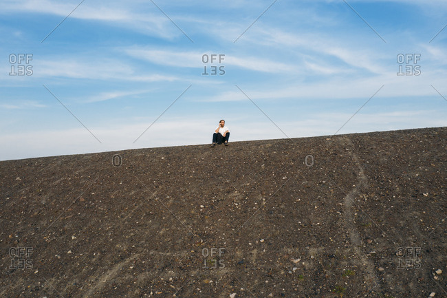 Low angle view of mature businessman sitting on hill against sky