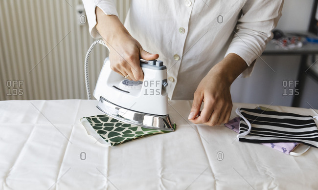 Midsection of woman ironing homemade mask on board