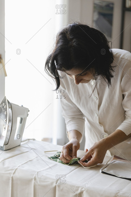 Woman holding homemade protective face mask on ironing board