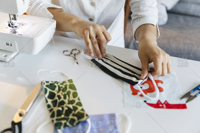 Midsection of woman preparing protective face mask by sewing machine at home