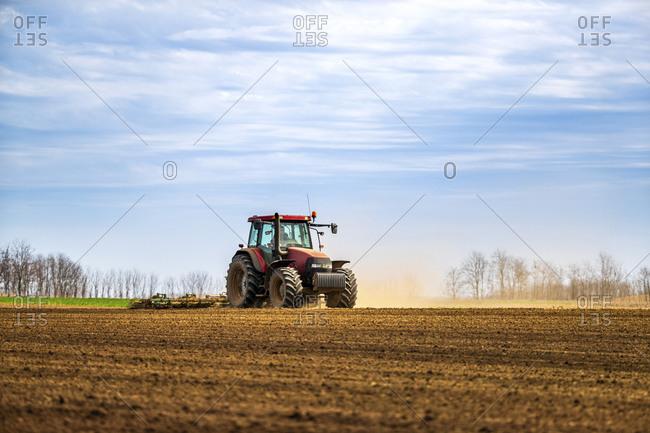 Farmer in tractor plowing field in spring