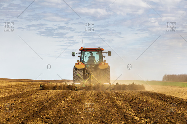 Back view of farmer in tractor plowing field in spring