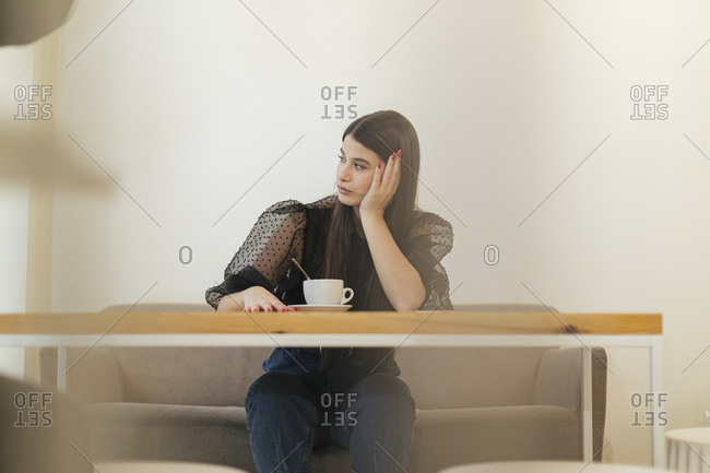 Thoughtful young woman looking away while sitting at cafe