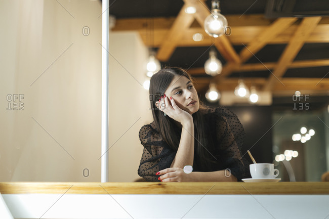 Thoughtful young woman sitting at table in illuminated coffee shop