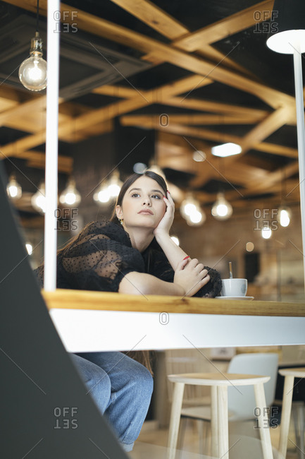 Thoughtful young woman leaning on table while looking away at illuminated cafeteria