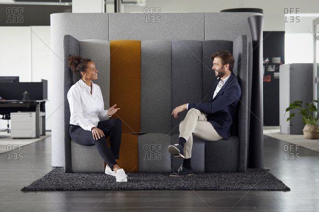 Colleagues keeping distance while talking together in office