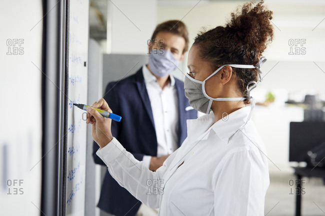Businessman looking at colleague writing on flip chart