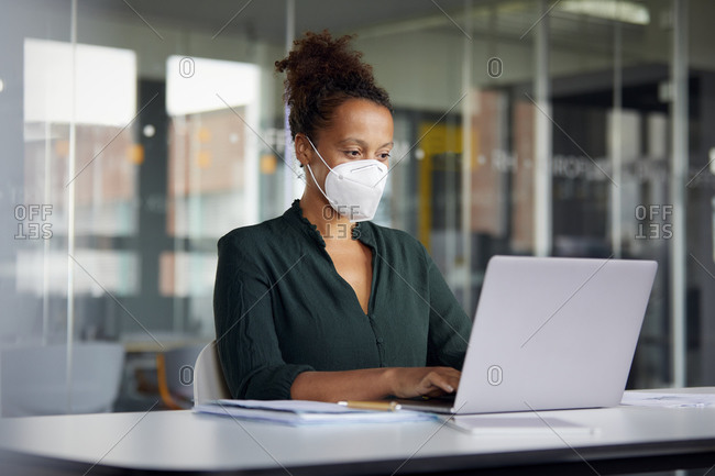 Portrait of businesswoman wearing protective mask working on laptop at counter