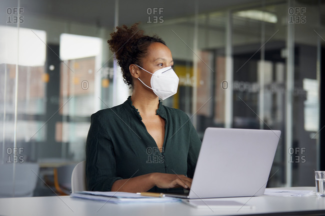 Portrait of businesswoman wearing  protective mask working on laptop at counter looking at distance