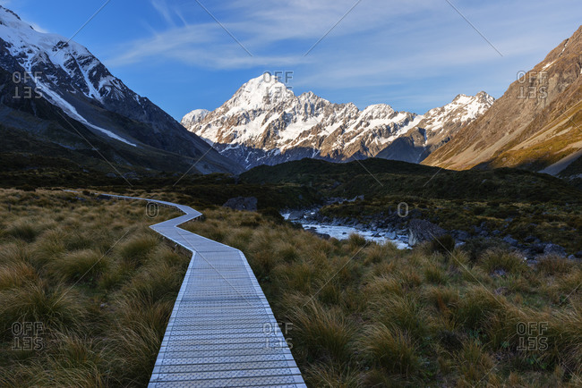 New Zealand- Canterbury- Boardwalk in Hooker Valley at dusk with Mount Cook in background