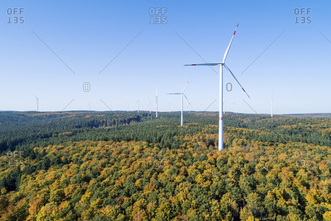 Germany- Baden-Wurttemberg- Drone view of clear sky over wind farm in autumn forest of Swabian Jura