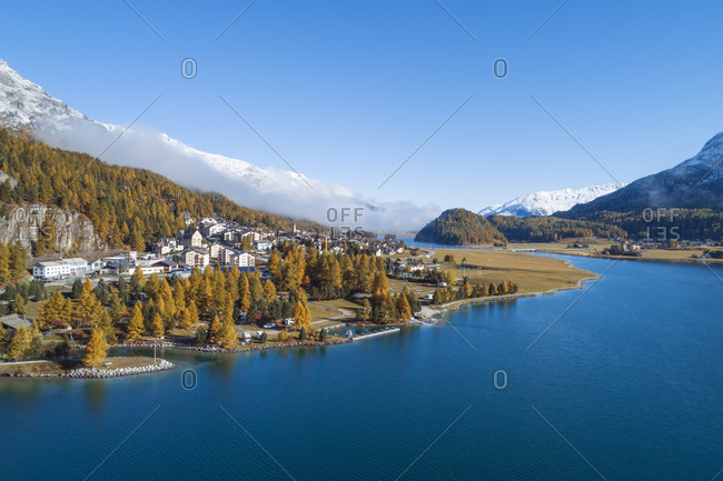 Switzerland- Canton of Grisons- Saint Moritz- Drone view of town on forested shore of LakeSilvaplanain autumn