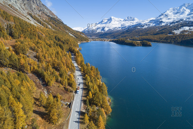 Switzerland- Canton of Grisons- Saint Moritz- Drone view of highway stretching along shore of Lake Sils in autumn