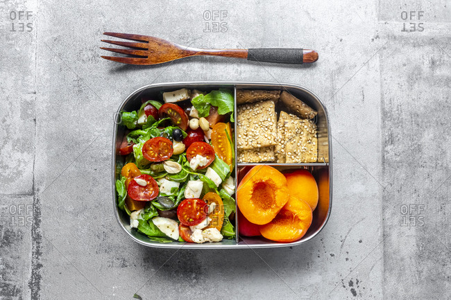 Lunch box with rocket salad with colored tomatoes- mozzarella and nuts- crispbread and apricots- wooden fork on concrete surface