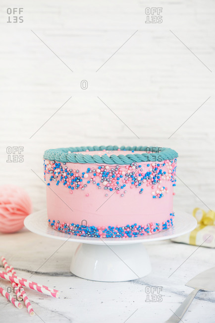 Pastel colored birthday cake on marble table