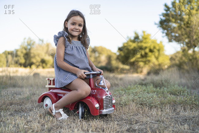 Portrait of smiling little girl with pedal car in nature
