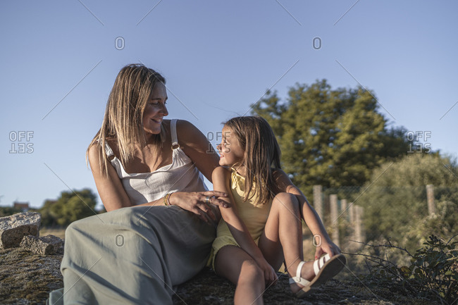 Mother and her little daughter enjoying sunlight in the evening