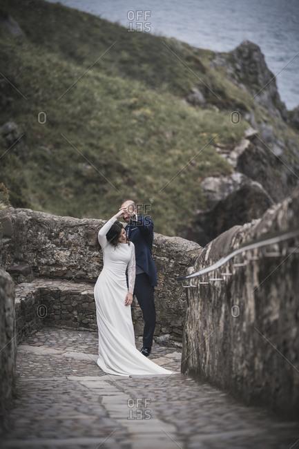Bridal couple dancing on way- Gaztelugatxe- Spain