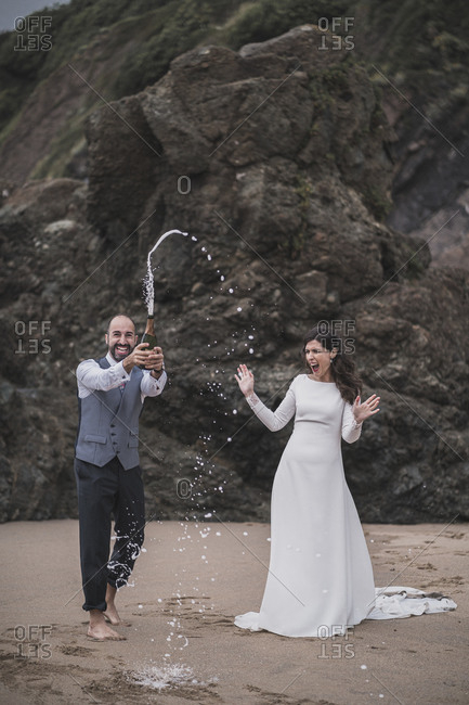 Bridal couple- man splashing with champagne at the beach