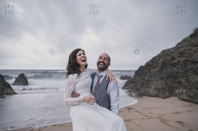 Laughing bridal couple at the beach- holding his wife
