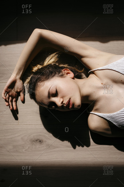 Directly above view of woman with eyes closed lying on hardwood floor at home