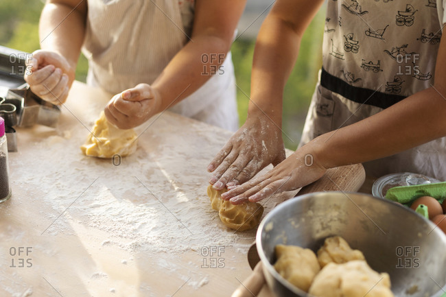 Crop view of two boys kneading dough