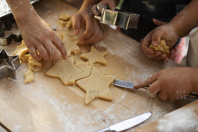 Crop view of children cutting out star shaped cookies