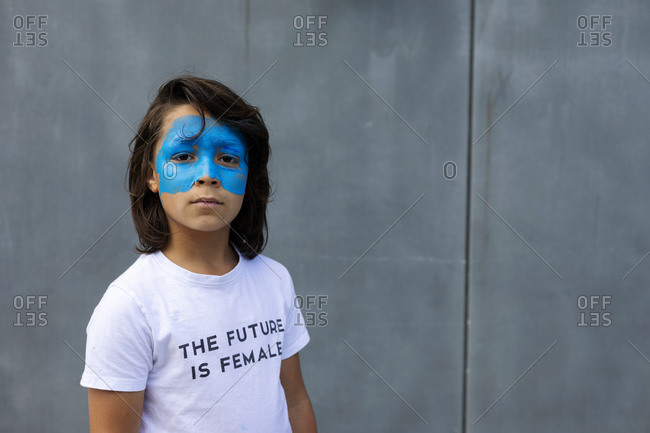 Portrait of boy with painted blue mask on his face wearing t-shirt with imprint 'The Future is Female'