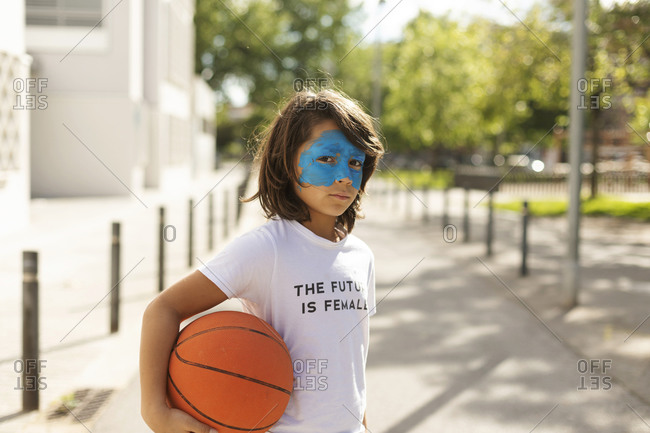 Portrait of boy with painted blue mask on his face holding basketball