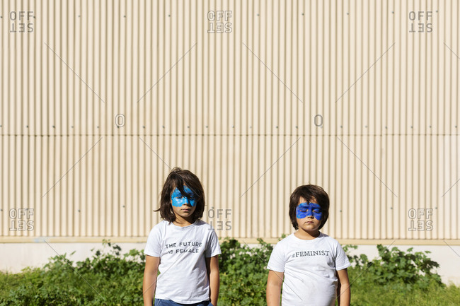 Two brothers with painted blue masks on their faces wearing t-shirts with feministic imprints