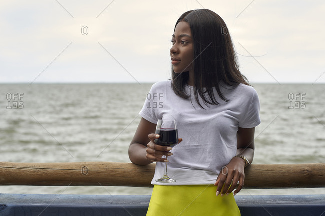 Portrait of young woman with glass of red wine in front of the sea