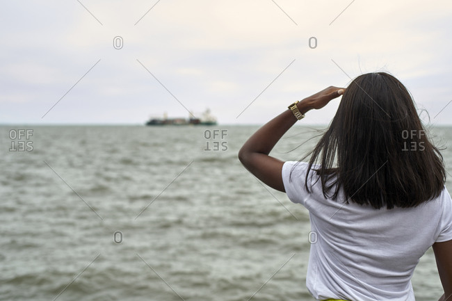 Back view of young woman in front of the sea looking to ship at horizon