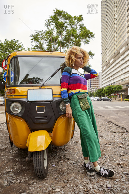 Full length young woman with afro hairstyle leaning on tuk-tuk in city