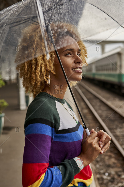 Side view of young woman with afro hairstyle enjoying monsoon while standing at railroad station