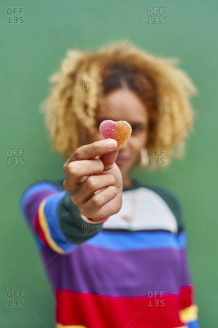 Young woman holding candy heart while standing against green wall