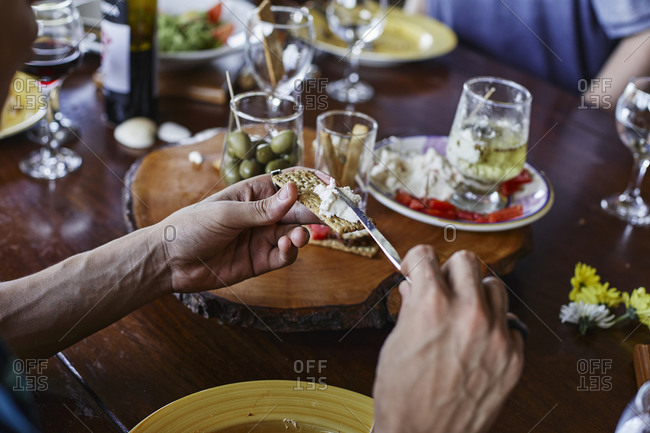 Cropped hands of man spreading cheese on cracker at dining table
