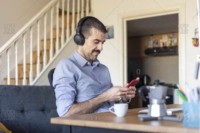 Man working from home- using smartphone with headphones during coffee break