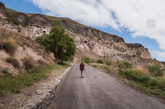 Georgia- Samtskhe-Javakheti- Male tourist walking along empty road leading toVardzia cave monastery