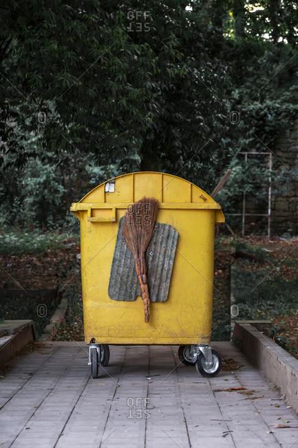 Georgia- Imereti- Kutaisi- Yellow garbage bin with broom