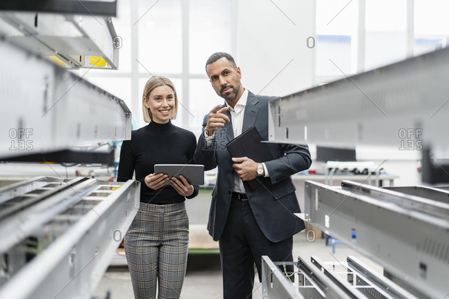 Businessman and woman with tablet at metal rods in factory hall