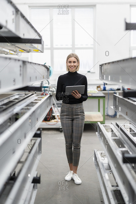 Woman holding tablet at metal rods in factory hall