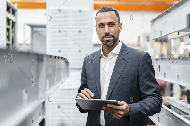 Portrait of confident businessman holding tablet at metal rods in factory hall