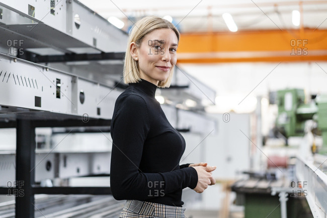 Portrait of smiling woman at metal rods in factory hall
